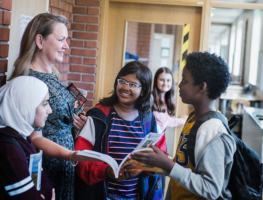 Elever och lärare pratar i en skolkorridor.