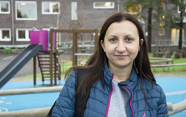 Porträttbild av en modersmålslärare med skolgård i bakgrunden.