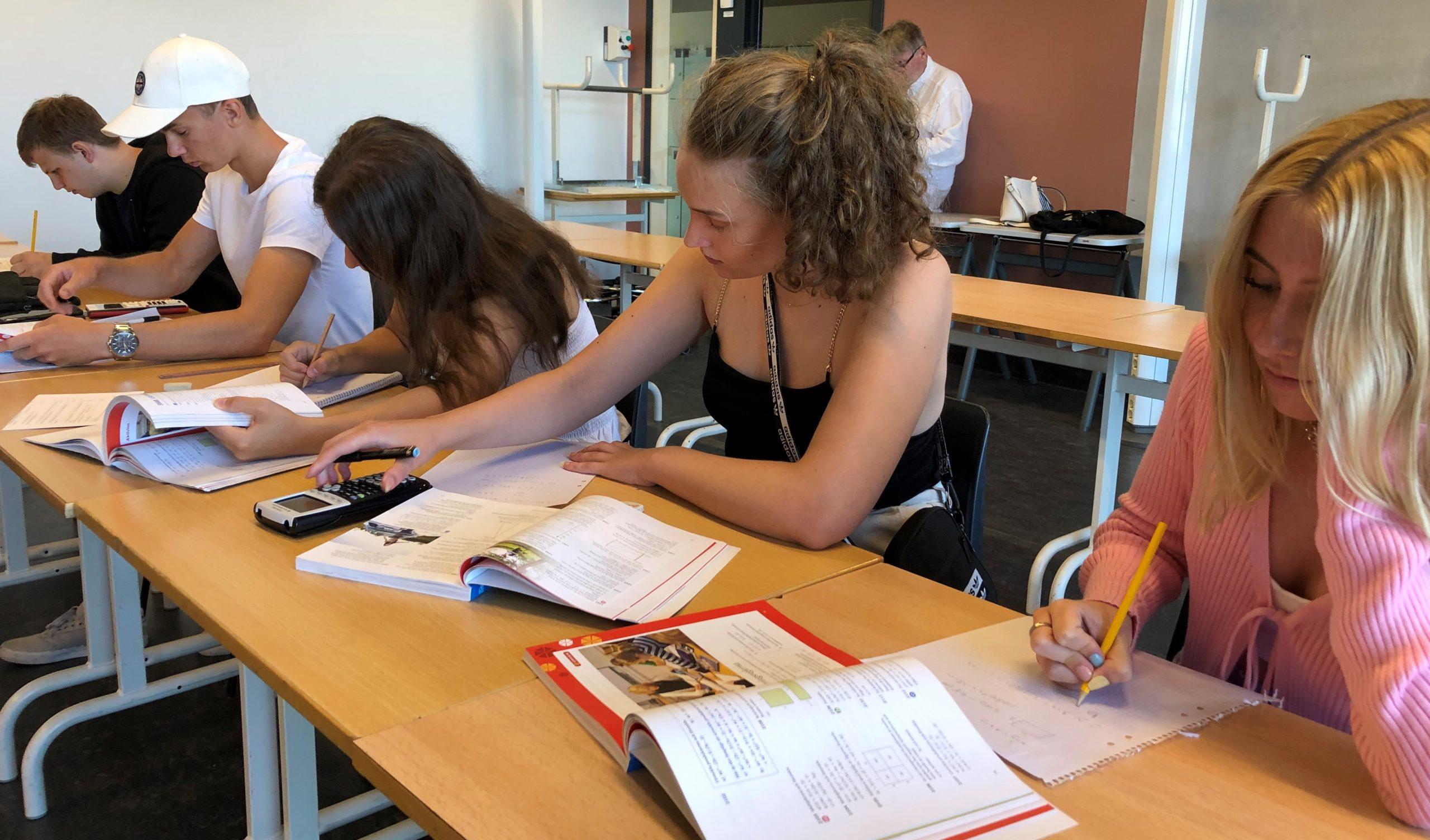 Fem av skolans elever sitter och gör skolarbete i ett klassrum.