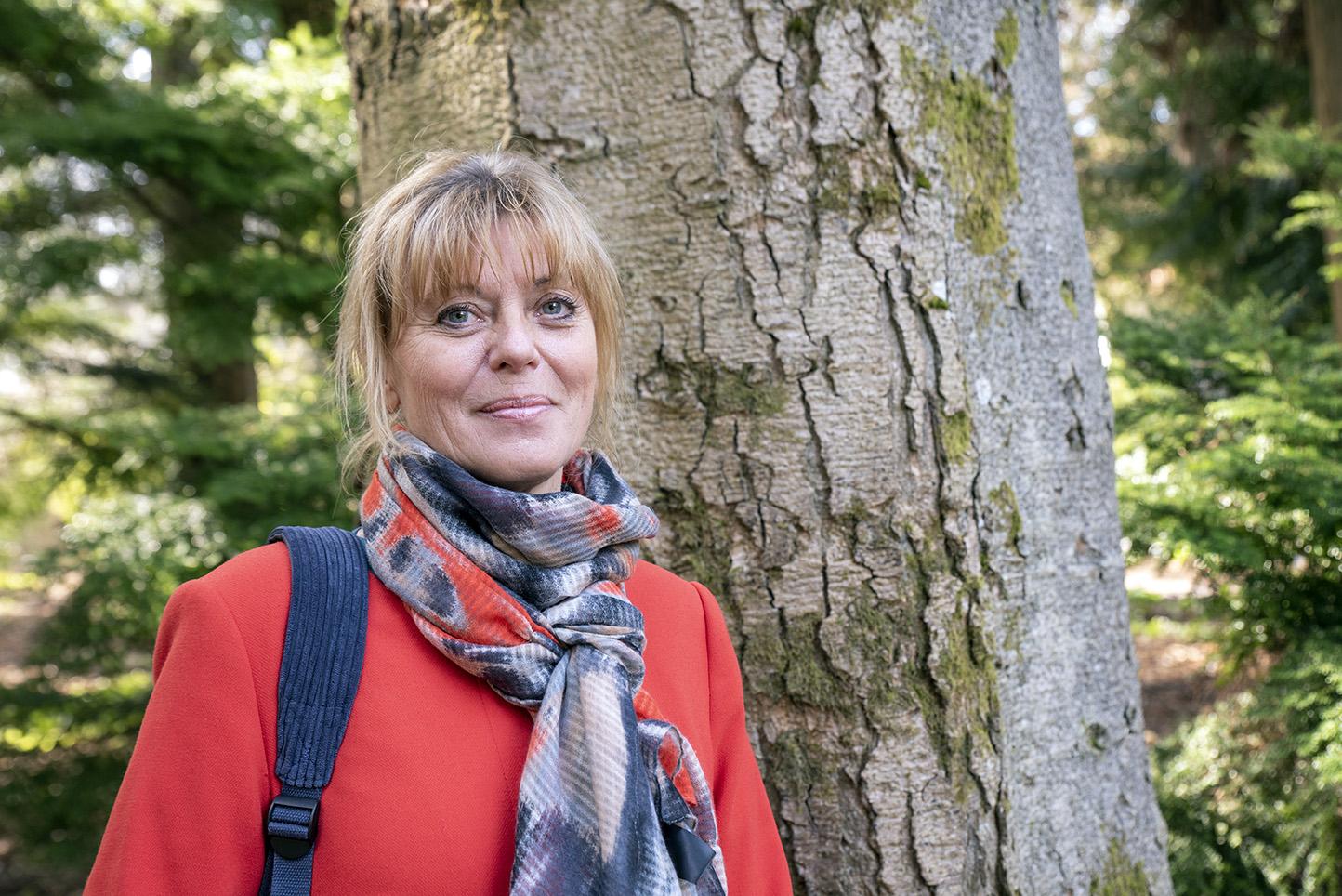 Porträttbild på Margaretha Häggström som står i en skogsmiljö.