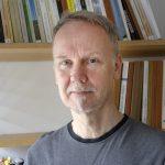 Porträttbild av Mats Widigson framför en bokhylla.