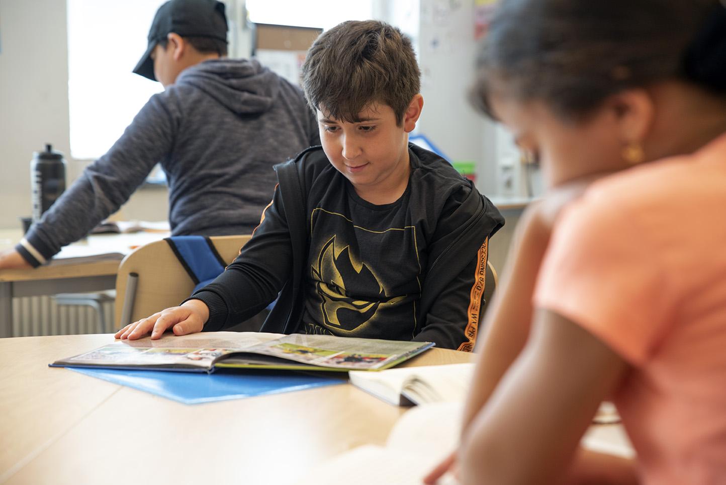 Tre elever sitter i ett klassrum och läser.