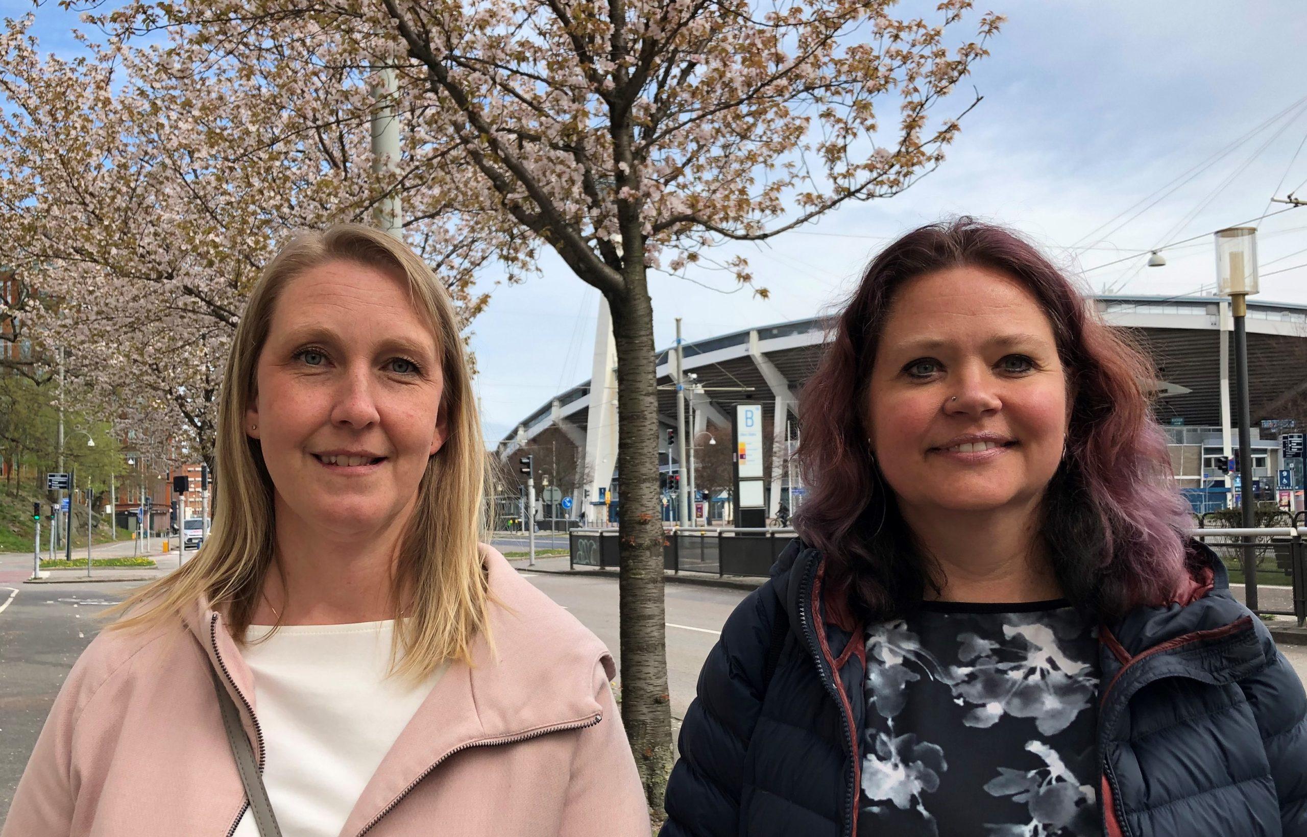 Barnskötarna Camilla Stalvik och Christina Malmström står bredvid varandra på Skånegatan, med blommande körsbärsträd i bakgrunden. och