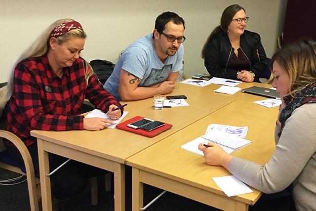 Fyra deltagare på lärledarutbildningen sitter vid ett bord och samtalar.