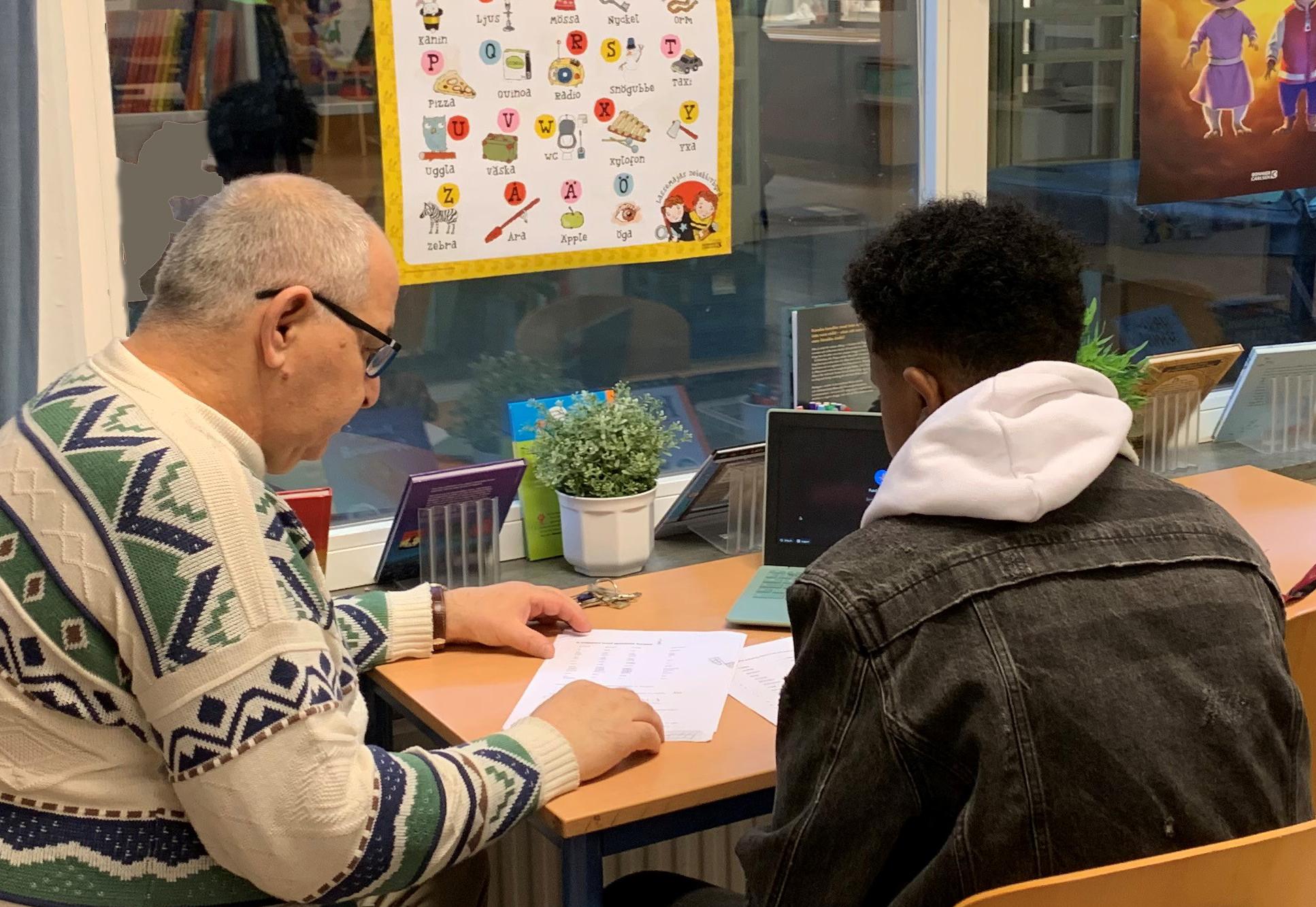 Studiehandledaren Abdul Hakim Abuali sitter tillsammans med en elev.