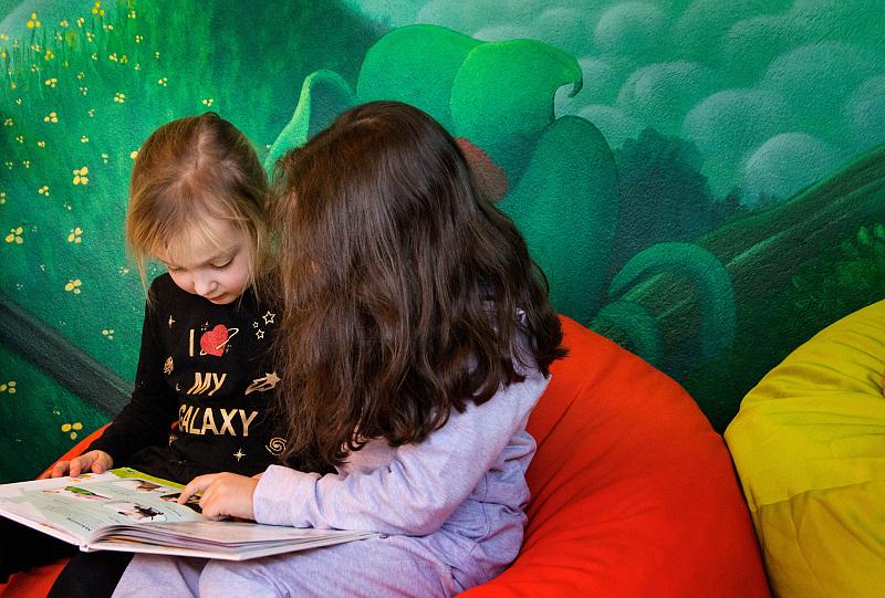 Två barn sitter bredvid varandra och läser i samma bok.